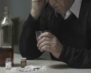 elderly-man-struggling-with-addiction-has-alcohol-and-pills-on-table