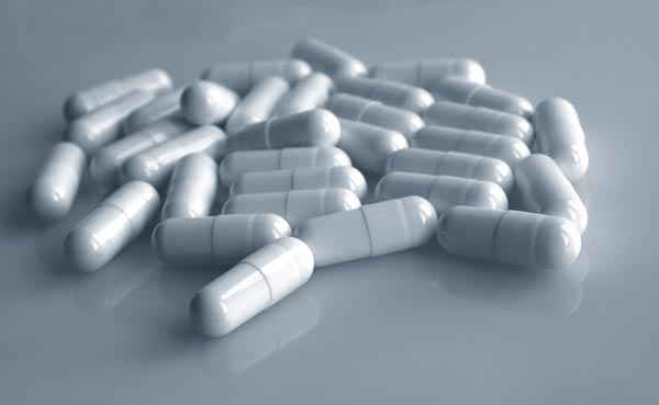 Vicodin pills strewn about a grey surface